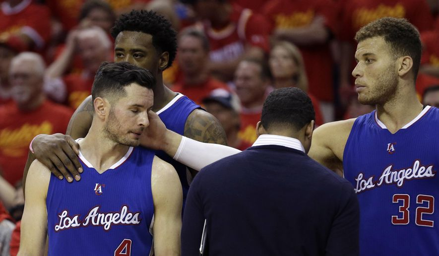 Los Angeles Clippers' Blake Griffin (32) reaches to touch the face of J.J. Redick (4) during the closing seconds of Game 7 of the NBA basketball Western Conference semifinals, Sunday, May 17, 2015, in Houston. The Rockets won 113-100. (AP Photo/David J. Phillip)