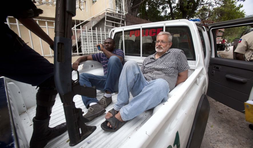FILE - In this Friday, Sept. 5, 2014, file photo, U.S. citizen Michael Karl Geilenfeld waits in handcuffs as the manager of his orphanage sits with him in the back of a police truck outside the St. Joseph's Home For Boys after police closed it down in the Delmas area of Port-au-Prince, Haiti. Haitian justice authorities said Monday, May 18, 2015, that they are making plans for a new criminal trial against Geilenfeld who has been accused of physically and sexually abusing boys in an orphanage that he has run for decades in the impoverished Caribbean country. (AP Photo/Dieu Nalio Chery, File)