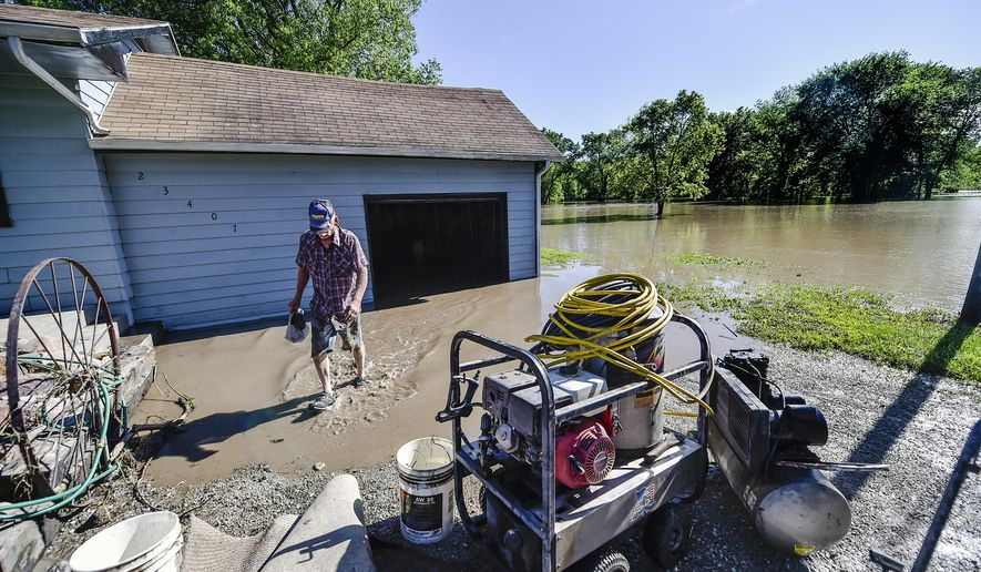 Tom Grider removes items from his flooded garage Sunday, May 17, 2015, in Mosby, Mo. About 35 homes took on water Sunday after the Fishing River overran its banks in Mosby, a town of about 190 residents located about 20 miles northeast of Kansas City, Clay County Sheriff's Department Lt. Will Akin said. (Allison Long/The Kansas City Star via AP)