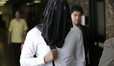 New York Police detective Wojciech Braszczok covers his face as he leaves a court room in New York on May 5, 2015. (Associated Press) **FILE**