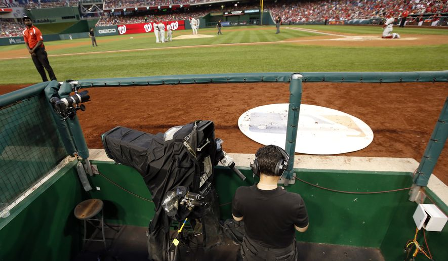 A MASN network videographer checks his phone after technical problems forced the network to use a different feed for several innings of a baseball game between the Washington Nationals and the Philadelphia Phillies at Nationals Park Saturday, Aug. 2, 2014, in Washington. (AP Photo/Alex Brandon) **FILE**