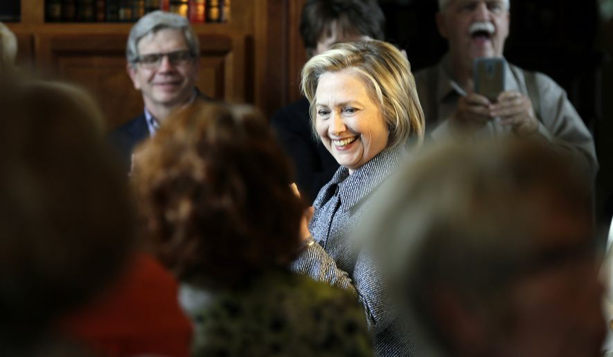 Democratic presidential candidate Hillary Rodham Clinton smiles as she is greeted before speaking at a gathering at the home of Dean Genth and Gary Swenson, Monday, May 18, 2015, in Mason City, Iowa. (AP Photo/Charlie Neibergall)