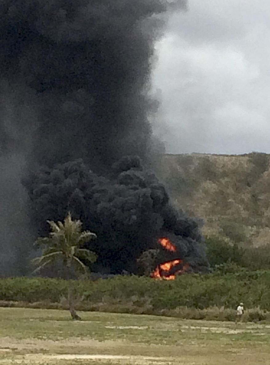 In this May 17, 2015, photo, smoke rises from a Marine Corps Osprey aircraft after making a hard landing near Bellows Air Force Station near Waimanalo, Hawaii. The fatal crash of the Marine Corps' new hybridized airplane-and-helicopter aircraft during a training exercise is renewing safety concerns about the machine. (Zane Dulin via AP)