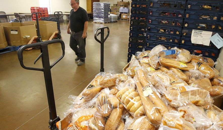 Randy Finley, the operations manager at The Church on Fillmore, walks past some bread after it was delivered at the food pantry at the church Monday, May 18, 2015, in Phoenix.  Hundreds of families line up on Tuesdays to get food and clothing from the thrift shop at the church. (AP Photo/Ross D. Franklin)