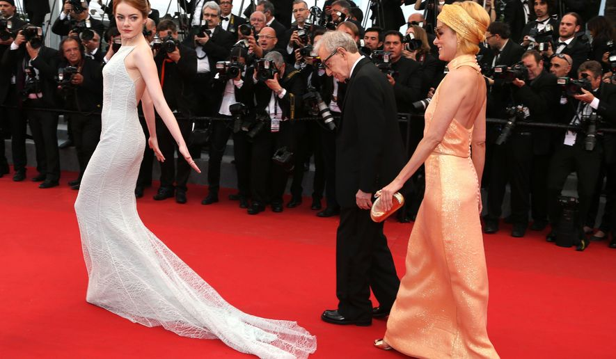 Actress Emma Stone, director Woody Allen and Parker Posey pose for photographers on the red carpet at the screening of the film Irrational Man at the 68th international film festival, Cannes, southern France, Friday, May 15, 2015. (AP Photo/Thibault Camus)