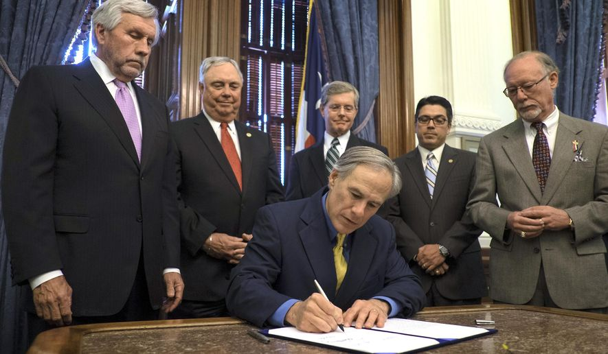 Texas Gov. Greg Abbott, front center, signs a fracking bill into law at the State Capitol in Austin, Texas, Monday, May 18, 2015. Abbott has signed into law a prohibition on cities and towns imposing local ordinances preventing fracking and other potentially environmentally harmful oil and natural gas activities. (Rodolfo Gonzalez/Austin American-Statesman via AP)