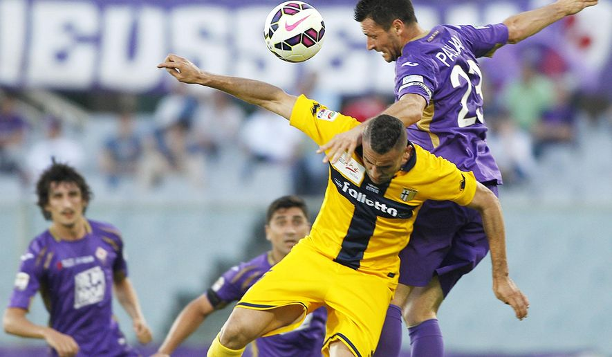Fiorentina's Manuel Pasqual, top, jumps for the ball with Parma's Abdelkader Ghezzal during a Serie A soccer match between Fiorentina and Parma at the Artemio Franchi stadium in Florence, Italy, Monday, May 18,  2015. (AP Photo/Fabrizio Giovannozzi)