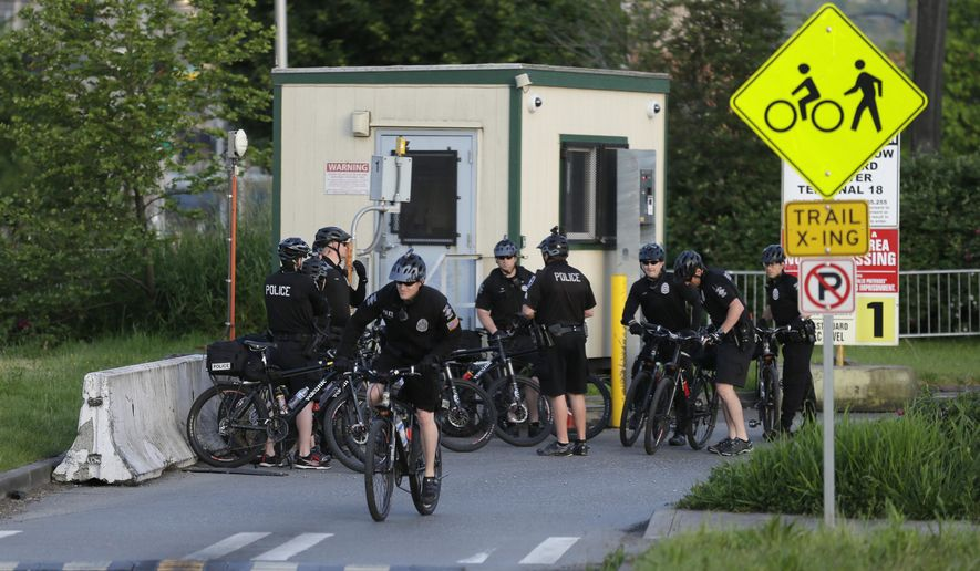 Police on bicycles gather at an entrance to a Port of Seattle facility, Monday, May 18, 2015, in Seattle, near the site where a protest against Arctic oil drilling was planned for later in the morning. Demonstrators have been showing opposition to a lease agreement between Royal Dutch Shell and the Port of Seattle to allow Shell's oil drilling equipment to be based in Seattle. (AP Photo/Ted S. Warren)