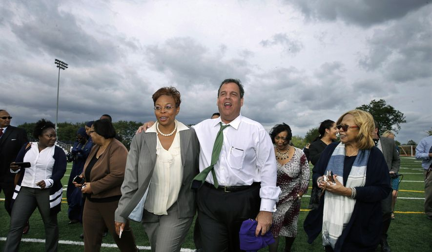 FILE -  In this Wednesday, Sept. 24, 2014 file photograph, Camden Mayor Dana Redd, center left, and Gov. Chris Christie walk together on a football field at Camden High School in Camden, N.J. The people of Camden don't have much say when it comes to the future of the city or its most important institutions, a situation that activists say is anti-democratic and also could be preventing city political and community leaders from developing experience with making big decisions.  (AP Photo/Mel Evans, File)