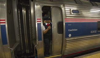 Amtrak assistant conductor Kellie Stiggers is shown working as Train 110 leaves Philadelphia's 30th Street Station for New York's Penn Station on May 18, 2015. It was the first northbound train from the city since a May 12 derailment killed 8 people and injured dozens. (Associated Press) **FILE**