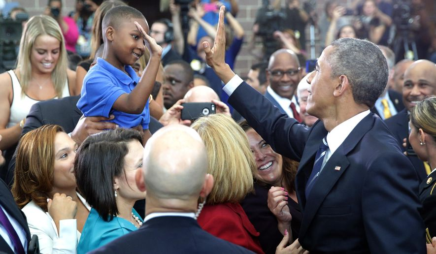 President Barack Obama high-fives Jaiden Steele, of Camden, after he spoke at the Ray & Joan Kroc Corps Community Center, Monday, May 18, 2015, in Camden, N.J. Obama traveled to Camden to visit with local law enforcement, meet with young people in the Camden community and tour the Real-Time Tactical Operation Intelligence Center at the Camden County Police Dept. headquarters. (Tim Hawk/South Jersey Times via AP)