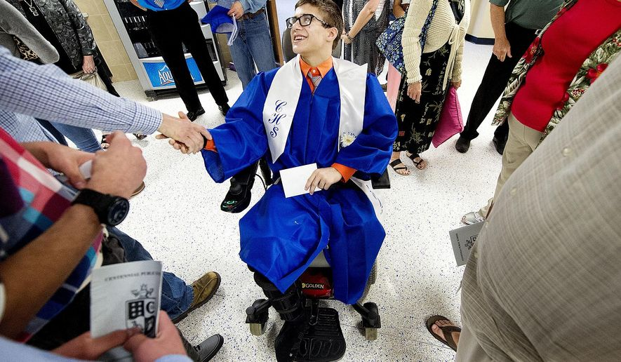 Surrounded by friends and family, Centennial High School senior Doyle Trout accepts well-wishes following graduation on Saturday, May 16, 2015. Trout, a four-time state wrestling champion who lost his left leg in an accident, is going to the University of Wyoming on a wrestling scholarship. Wyoming is honoring Trout's scholarship, and he hopes to wrestle again someday but doing that won't be easy.(Francis Gardler/The Journal-Star via AP) LOCAL TELEVISION OUT; KOLN-TV OUT; KGIN-TV OUT; KLKN-TV OUT