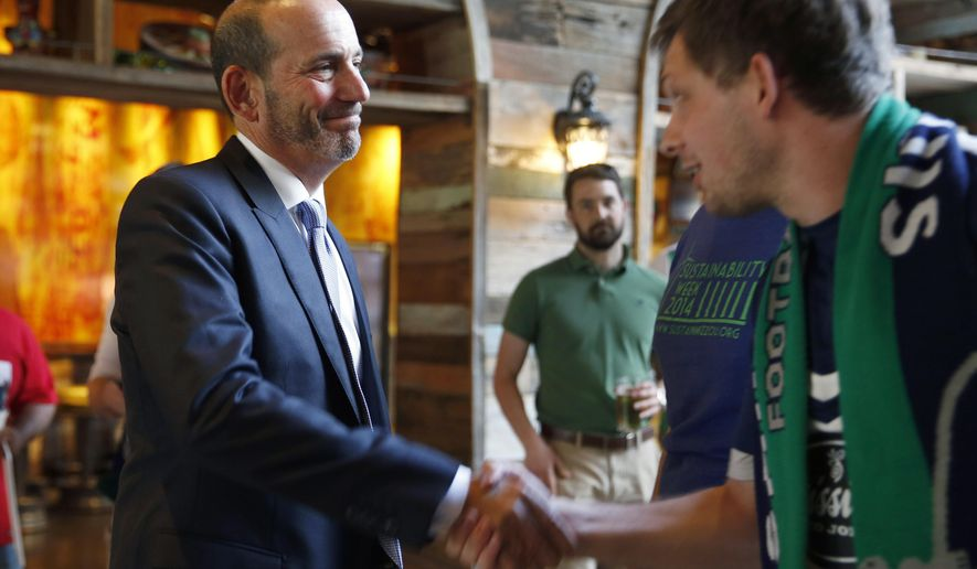 Major League Soccer commissioner Don Garber, left, shakes hands after speaking to a gathering of soccer fans Tuesday, May 19, 2015, in St. Louis. Garber is visiting St. Louis to meet with officials and assess its potential as an MLS expansion city. (AP Photo/Jeff Roberson)