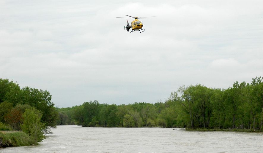 A helicopter searches the South Platte River just west of the Buffalo Bill Road Bridge, Tuesday, May 19, 2015, in North Platte, Neb. Authorities are searching the river in western Nebraska, looking for two people who reportedly drove into the rushing water the night before. (Joe Volcek/The Telegraph via AP)