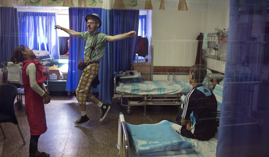 In this Wednesday, May 13, 2015 photo, Palestinian siblings Ahmed, right, and Hadeel Hamdan watch medical clown who goes by the name 'Juhl' perform, at the Rambam Health Care Campus in Haifa, Israel. The bedroom of Palestinian Ahmed and Hadeel looks like a hospital ward, filled with beeping machines, monitors, solution bags and sterilizing fluids. This is where the Gaza teenagers spend 12 hours a day connected to dialysis machines. These contraptions and their hopes for a better life come from a surprising source: an Israeli hospital. (AP Photo/Ariel Schalit)