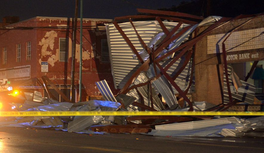 Debris from the roof of the Poston Building lies on an abandoned bank after a tornado went through the area in Mineral Wells, Texas, Tuesday, May 19, 2015. Moderate damage was widespread, but emergency officials say the worst damage appeared to be downtown.  (Bob Haynes/The Fort Worth Star-Telegram via AP)  MAGS OUT