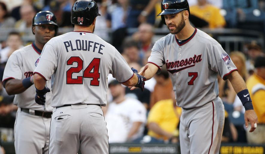 Minnesota Twins' Trevor Plouffe (24) is greeted by Joe Mauer (7) who scored on his two-run home run off Pittsburgh Pirates starting pitcher Francisco Liriano during the second inning of a baseball game in Pittsburgh on Tuesday, May 19, 2015. (AP Photo/Gene J. Puskar)