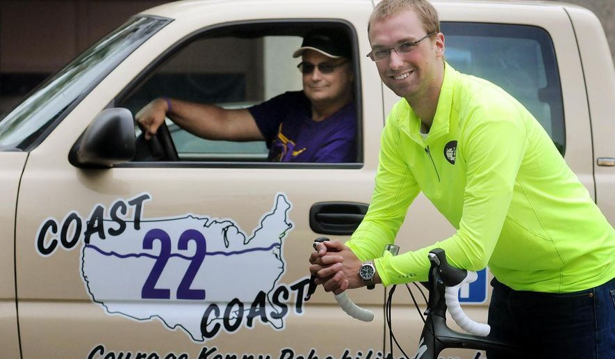 In this Monday, May 18, 2015 photo, Blaine Kolstad, foreground, and Abe Kolstad pose for a photograph in Mankato, Minn., before embarking on a cross-country bike trip to raise money for people with brain and spinal cord injuries. They are the brother and son, respectively, of Isaac Kolstad, who suffered a brain injury during an assault in May 2014. (John Cross/The Free Press via AP)