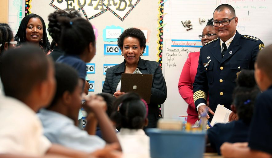 U.S. Attorney General Loretta Lynch, center, and Cincinnati Police Chief Jeffery Blackwell visit a third grade class at Chase Elementary in Cincinnati onTuesday May 19, 2015.  Lynch began a national tour highlighting collaborative programs and policing practices designed to improve public safety and strengthen police-community relations.  The Justice Department says the tour is intended to promote $163 million in grants available to build on President Barack Obama's commitment to work with law enforcement and others to implement recommendations from the 21st Century Policing Task Force report.(Cara Owsley/The Cincinnati Enquirer via AP)  MANDATORY CREDIT;  NO SALES