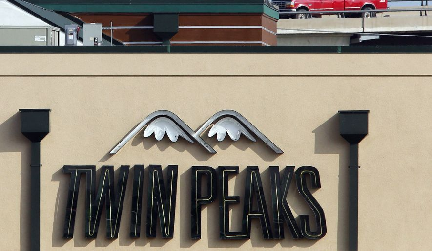 Law enforcement officers stand sentry atop the Twin Peaks restaurant in Waco, Texas, where Sunday's deadly shootout between rival motorcycle gangs left 9 dead and 18 more injured. The chain's Dallas headquarters announced the Waco location would have its franchise agreement yanked due to what it called improper security. (Jerry Larson/Waco Tribune-Herald/Associated Press)