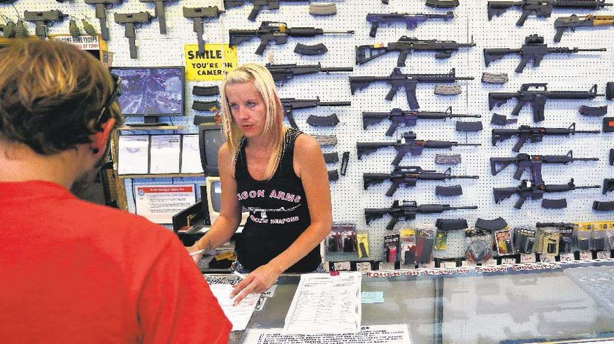 An employee at a gun store in Colorado assists a customer. (Associated Press) ** FILE **