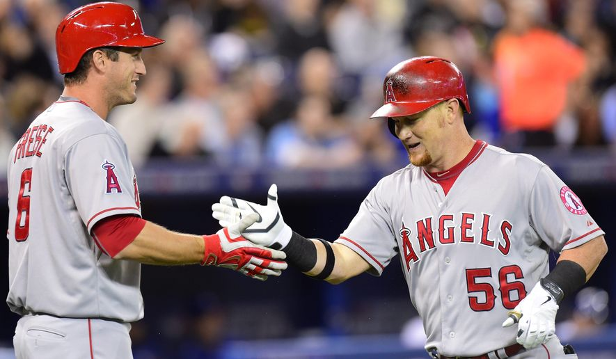 Los Angeles Angels' Kole Calhoun (56) celebrates with teammate David Freese after hitting a home run against the Toronto Blue Jays during fourth inning American League baseball action in Toronto, Tuesday, May 19, 2015. (Frank Gunn(/The Canadian Press via AP) MANDATORY CREDIT