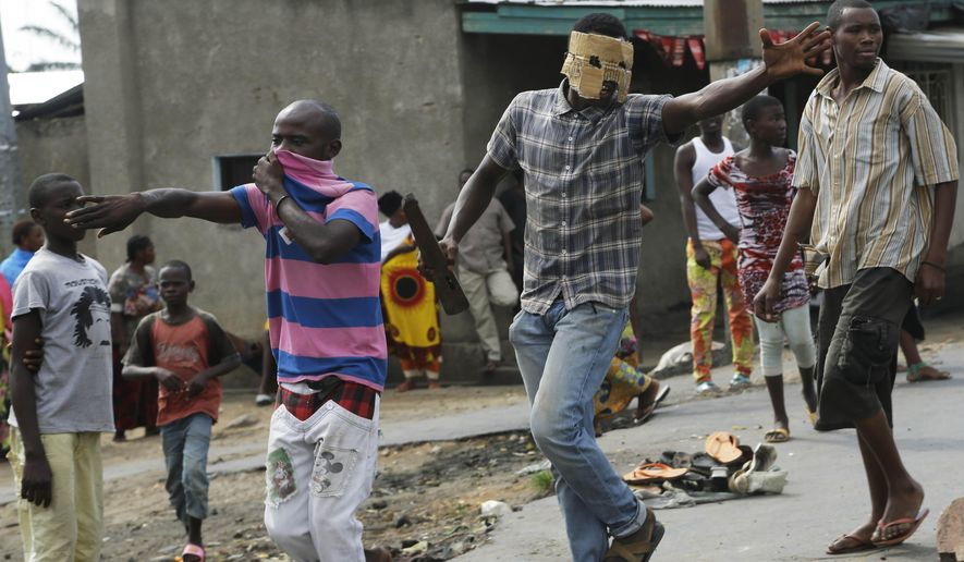 Demonstrators call on people to join them in the Cibitoke neighborhood of Bujumbura, Burundi, Tuesday May 19, 2015. Protesters have been demonstrating for the last three weeks opposing the president's bid for a third term. (AP Photo/Jerome Delay)