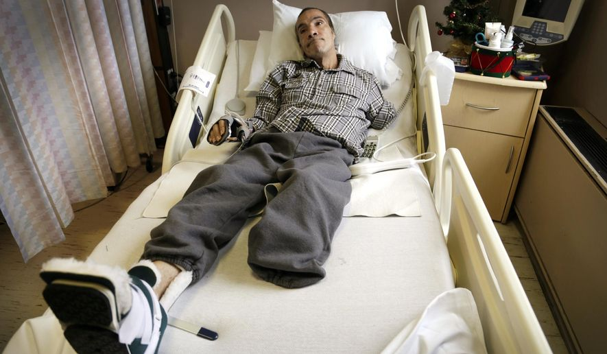 FILE - In this Dec. 9, 2014 file photo, Steve Constantine recalls a vicious dog attack from his hospital bed in Detroit. A judge on Tuesday, May 19, 2015, awarded a $100 million civil judgment to Constantine who lost most of his left arm, his left leg below the knee and his left ear after after he was mauled as he tried to feed a friend's dogs in Detroit. Police killed one dog at the scene and said they rounded up at least 11 other pit bulls or pit bull mixes that were later euthanized. (Mandi Wright/Detroit Free Press via AP, File)  DETROIT NEWS OUT; TV OUT; MAGS OUT; NO SALES; MANDATORY CREDIT DETROIT FREE PRESS