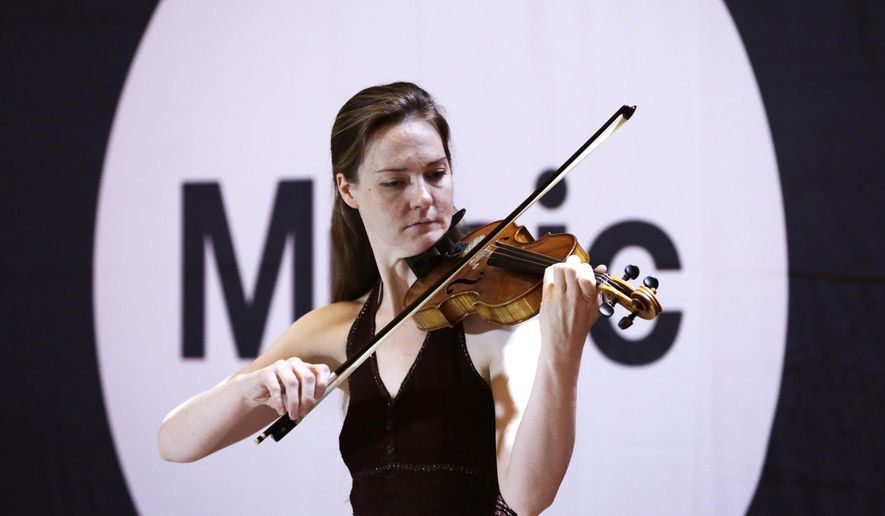 """Rebekah Butler, whose stage name is """"Becka Jay,"""" plays solo violin as she auditions for judges in Grand Central Terminal's Vanderbilt Hall in New York, Tuesday, May 19, 2015. Butler was among a group of about 70 potential subway performers seeking official permission to set up their acts on an underground platform or walkway to entertain New York city's commuters. (AP Photo/Kathy Willens)"""