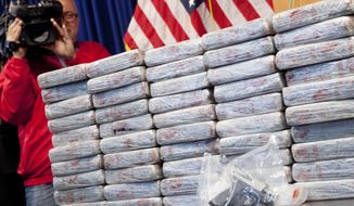 A firearm and 154 pounds of heroin worth at least $50 million are displayed at a Drug Enforcement Administration news conference, Tuesday, May 19, 2015 in New York. The DEA called the heroin seizure its largest ever in New York state. Officials said on Tuesday that most of the drugs were found in an SUV in the Bronx following a wiretap investigation. (AP Photo/Mark Lennihan)