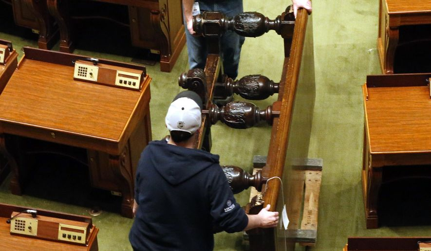 Worker move a table from the retiring room of the Minnesota House as the chamber is cleared, Tuesday, May 19, 2015, in St. Paul, Minn., as restoration of the State Capitol continues following the midnight adjournment of the 2015 session adjourned. (AP Photo/Jim Mone)