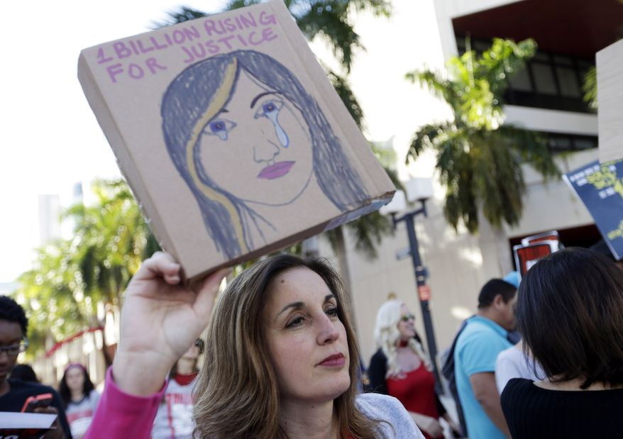 Lynette McGuinness holds a sign during a rally against human trafficking Friday, Feb. 14, 2014, in Miami. This event was part of the One Billion Rising for Justice, a worldwide event by supporters demanding the arrest of those who participate in domestic violence and human trafficking. (AP Photo/Lynne Sladky) ** FILE **