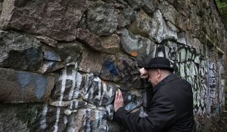 In this photo taken on Wednesday, May 13, 2015, Shmuel Levin, the chairman of the Jewish religious Community of Vilnius and Lithuania, leans against a wall of the power substation built of tombstones from a Jewish cemetery in Vilnius, Lithuania. Tombstones from a Jewish cemetery were used to build a power substation in the 1960s. (AP Photo/Mindaugas Kulbis)
