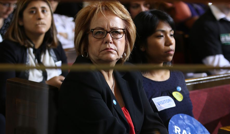 Maria Elena Durazo, an official at the national labor organization Unite Here and former head of the Los Angeles County Federation of Labor, center, and Ilse Escobar, program director at the Miguel Contreras Foundation, listen to motions as the Los Angeles City Council votes to raise the minimum wage in the city to $15 an hour by 2020, making it the largest city in the nation to do so, in Los Angeles Tuesday, May 19, 2015. The measure approved Tuesday calls for small businesses with 25 or fewer employees to have an additional year to reach the $15 plateau. The council voted 14-1 after members of the public made impassioned statements for and against the plan. The increases begin with a wage of $10.50 in July 2016, followed by annual increases to $12, $13.25, $14.25 and then $15. Small businesses and nonprofits would be a year behind. (AP Photo/Damian Dovarganes )