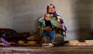In this picture taken, Wednesday, May 6, 2015, Syrian refugee Fatmeh Ahmed, 20, holds her 10-month-old son, Hassan, in their shack on a peach farm near the northern Jordanian community of Salhiyeh. Ahmed, and her husband live on $9-a-day jobs on the farm, after they  lost $100 a month in food vouchers due to cuts by the cash-strapped World Food Program. (AP Photo/Raad Adayleh)
