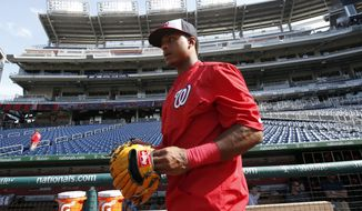 Washington Nationals shortstop Wilmer Difo (1) puts on his glove for batting practice before an interleague baseball game against the New York Yankees at Nationals Park, Tuesday, May 19, 2015, in Washington. (AP Photo/Alex Brandon)