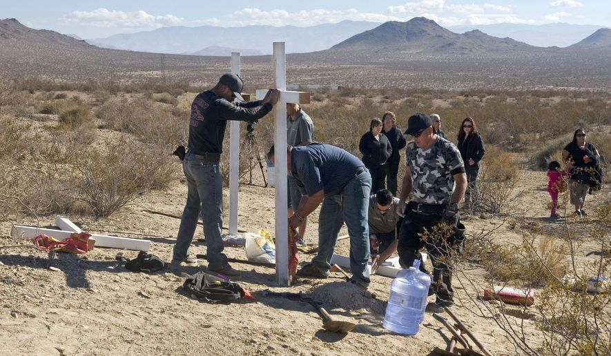 """FILE - In this Nov. 20, 2013, file photo, residents of Victorville, Calif., and surrounding communities place crosses near the graves where the McStay family was found in Victorville, Calif. Prosecutors are expected to reveal Tuesday, May 19, 2015, the evidence that led them to Charles """"Chase"""" Merritt,  the sole suspect in the case, at a preliminary hearing. A judge previously denied a media request to unseal investigative filings and authorities have said little about the murders of Joseph McStay, 40, his wife, Summer, 43, and their sons, 4-year-old Gianni and 3-year-old Joseph Jr. (James Quigg/The Victor Valley Daily Press via AP, File)"""