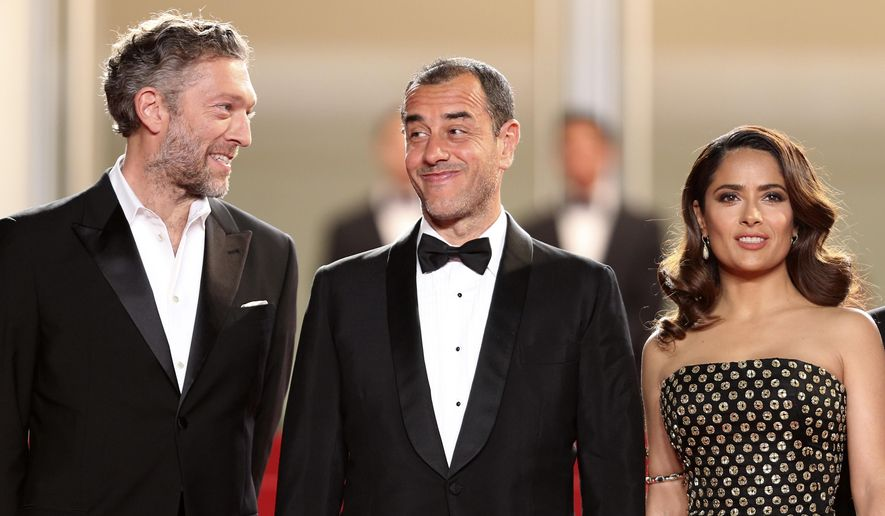 Actor Vincent Cassel, left, speaks with director Matteo Garrone, as they arrive with actress Salma Hayek for the screening of the film Tale of Tales at the 68th international film festival, Cannes, southern France, Thursday, May 14, 2015. (AP Photo/Thibault Camus)