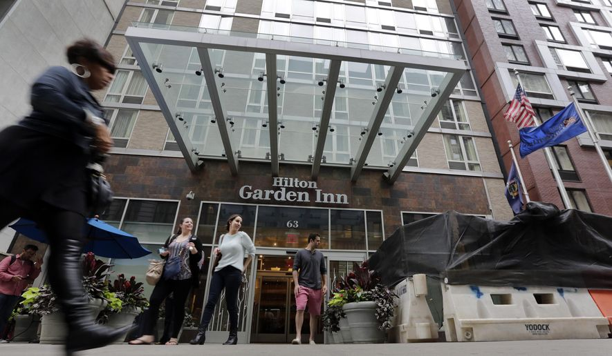 People leave the Hilton Garden Inn, in New York, Monday, May 18, 2015. New York City police are investigating the death of a man found unconscious, with a head injury, under a mattress at the hotel, blocks from the Empire State Building. (AP Photo/Richard Drew)