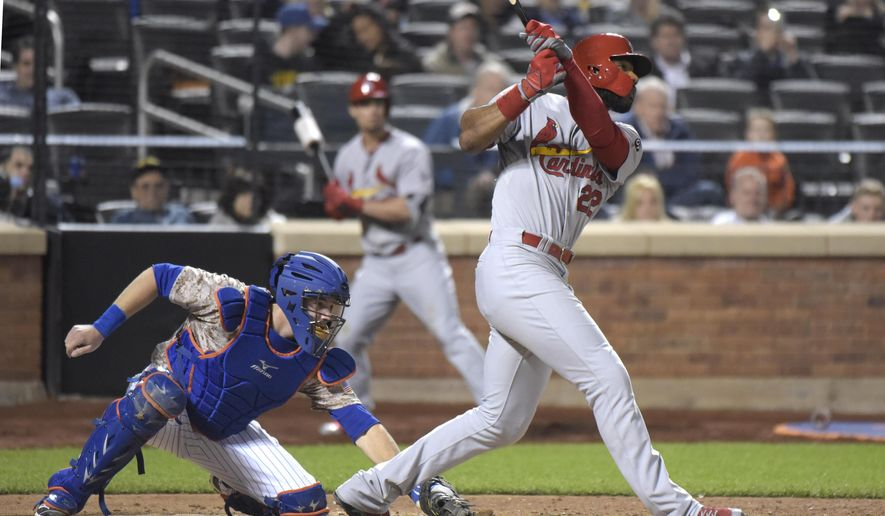 St. Louis Cardinals' Jason Heyward hits a sacrifice fly to score a run as New York Mets catcher Kevin Plawecki, left, looks on during the ninth inning of a baseball game Monday, May 18, 2015, at Citi Field in New York. (AP Photo/Bill Kostroun)