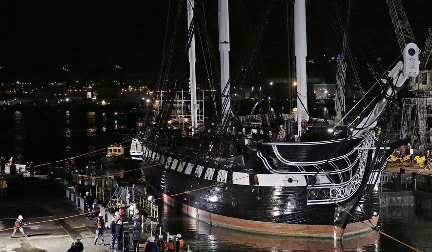 Workers steady lines as the USS Constitution is guided into a dry dock in Boston, Monday, May 18, 2015. The world's oldest commissioned warship still afloat, which was launched in 1797, will under go a major restoration project, which is expected to take years and as much as $15 million to complete. (AP Photo/Charles Krupa)