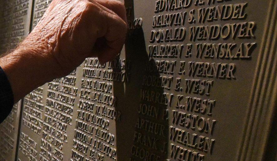 WWII veteran John Symons, and J.L. Hudson's employee, puts his finger on his name on the commemorative plaque that was erected in downtown Detroit Hudson's in 1947 to pay tribute to the company's 1,146 World War II veterans, including 31 men who lost their lives, denoted by a small star next to their name, during the rededication of the J.L. Hudson's historic World War II commemorative plaque, originally at the downtown Detroit Hudson's, Tuesday, May 19, 2015, at the Oakland Mall Macy's in Troy, Mich.  (Daniel Mears/Detroit News via AP)  DETROIT FREE PRESS OUT; HUFFINGTON POST OUT