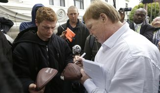 Oakland Raiders owner Mark Davis, right, autographs deflated footballs for Chase Bender outside of the NFL's spring meetings in San Francisco, Tuesday, May 19, 2015. (AP Photo/Jeff Chiu)