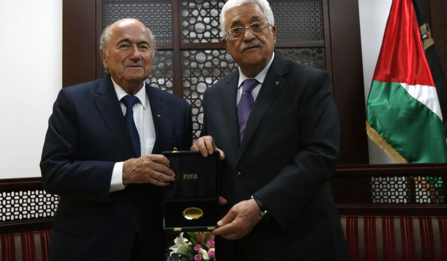"Palestinian President Mahmoud Abbas, right, receives a gift from FIFA President Sepp Blatter, during their meeting in the West Bank city of Ramallah, Wednesday, May 20, 2015. FIFA President Sepp Blatter said Tuesday he is on a ""mission of peace"" to resolve tensions between the Israeli and Palestinian soccer federations in the hope of staving off a Palestinian bid to oust Israel from the world governing body. (Mohamad Torokman/ Pool Photo via AP)"