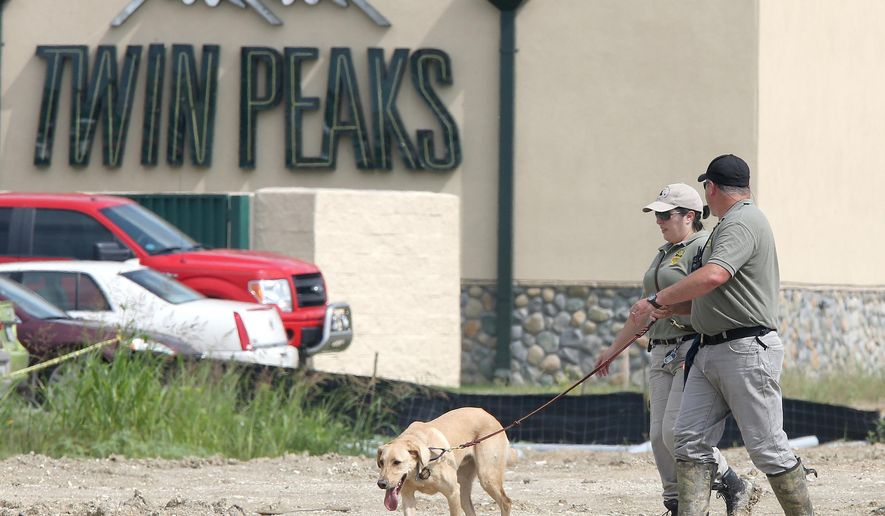 In this May 18, 2015, photo, authorities search a vacant lot near the Twin Peaks restaurant Monday, May 18, 2015, in Waco, Texas. About 170 members of rival motorcycle gangs were charged with engaging in organized crime Monday, a day after a shootout at a Twin Peaks killed nine people and wounded 18. (AP Photo/Jerry Larson)