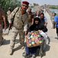 An Iraqi soldier helped one of thousands of Ramadi residents leave Wednesday after the city was seized by Islamic State fighters. Former trainers say Iraqi troops are in dire need of unity and leadership in government. (Associated Press)