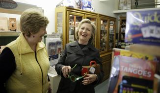 Democratic presidential candidate Hillary Rodham Clinton laughs with Laree Randall, owner of Laree's gift shop, as she looks at toys Tuesday, May 19, 2015, in Independence, Iowa. (AP Photo/Charlie Neibergall)