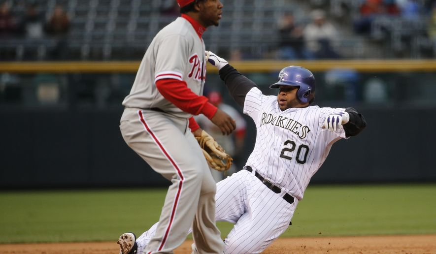 Colorado Rockies' Wilin Rosario (20) slides safely into third for a two run triple as Philadelphia Phillies third baseman Maikel Franco looks for the throw during the first inning of a baseball game Tuesday, May 19, 2015, in Denver. (AP Photo/Jack Dempsey)