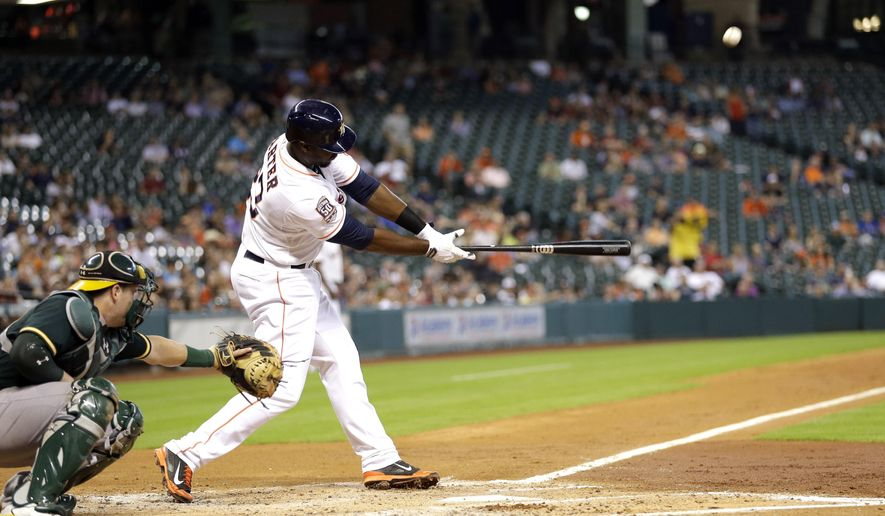 Houston Astros' Chris Carter (23) hits a two-run home run as Oakland Athletics catcher Stephen Vogt, left, reaches for the pitch during the second inning of a baseball game Tuesday, May 19, 2015, in Houston. Colby Rasmus scored on Carter's homer. (AP Photo/David J. Phillip)