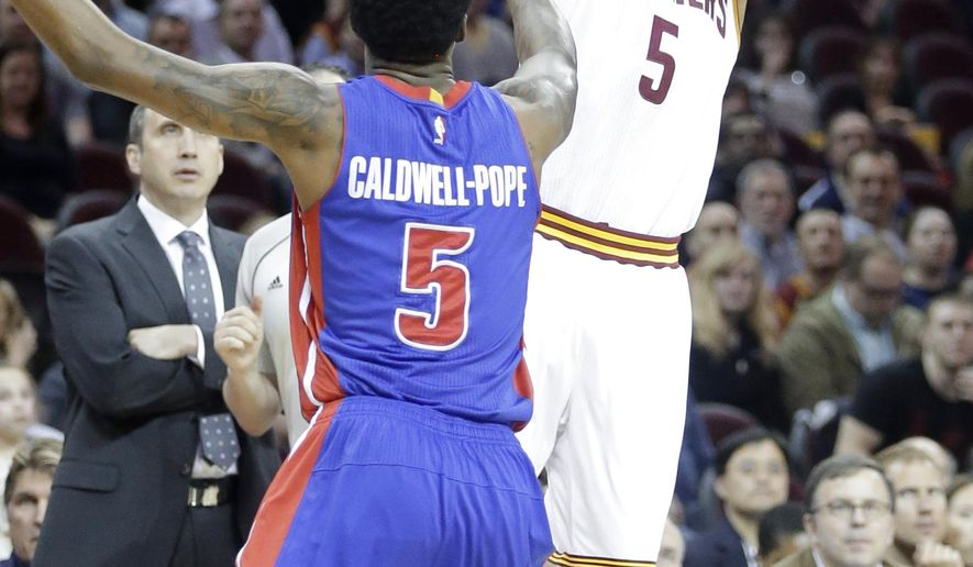 FILE - In this April 13, 2015, file photo, Cleveland Cavaliers' J.R. Smith, right, shoots over Detroit Pistons' Kentavious Caldwell-Pope in the first quarter of an NBA basketball game in Cleveland.  The enigmatic shooting guard, who came to the Cavaliers with the reputation of being diffcult, has found a new home in Cleveland and he's relishing the chance to be part of a team moving toward an NBA title. (AP Photo/Mark Duncan, File)